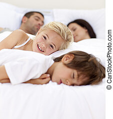 Little girl smiling on bed wile her family sleep