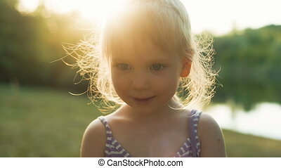 Little girl Sniffing flower at sunset