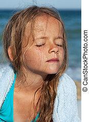 Little girl soaking up the sun on the windy sea shore -...