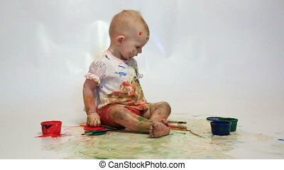 little girl soiled by multi-colored paints sees on a white background