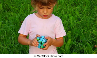 little girl solves rubik's cube on green grass background