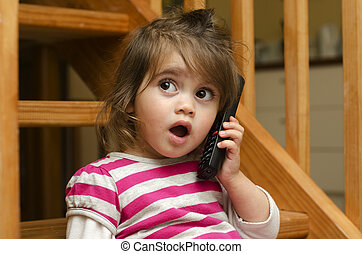 Little girl speak on the phone at home.