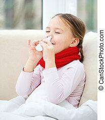 Little girl spraying her nose