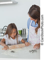 Little girl spreading a dough with a rolling spin in the...