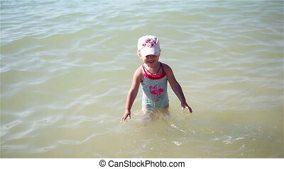 Little girl squirted with water in the sea