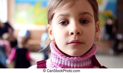 Little girl stand in childrens clinic among kids run around