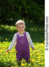 little girl stand on a glade with the blossoming dandelions