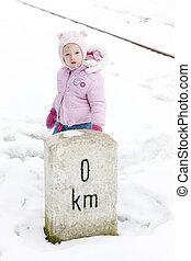 little girl standing at marker