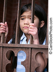 Little girl standing behind iron bars with sad expression,...