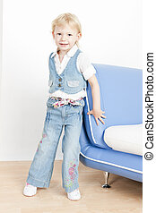 little girl standing by sofa