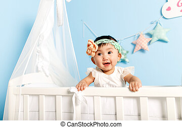 little girl standing in a crib
