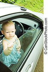 little girl standing in car