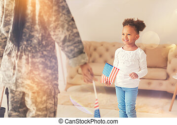 Little girl standing in front of her mother with American flag
