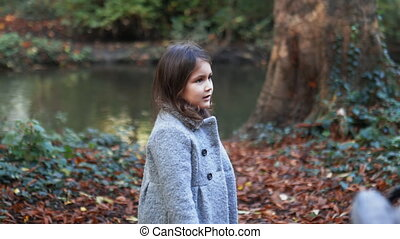 Little brunette girl in a gray coat standing next to a river suddenly starts running on a path covered in autumn leaves