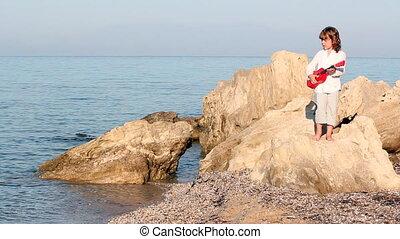 little girl standing on a rock