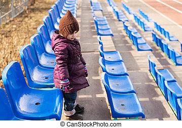 Little girl standing on a viewing stand