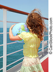 little girl standing on cruise liner deck and holding inflatable globe, half body, view from back