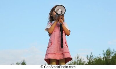little girl standing on hill and talking through megaphone