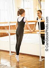 girl standing on tiptoe at dance class near mirror - Little...