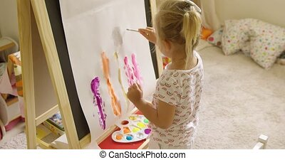 Little girl standing painting at an easel - Little blond...