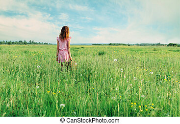 Little girl standing with suitcase on summer meadow