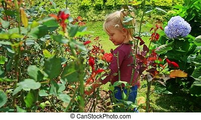 Little Girl Stands among Flowers Touches Petals in Park