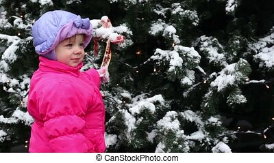 girl stands and hold bow ribbon on Christmas tree covered with snow