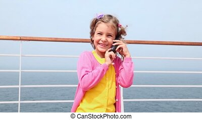 Little girl stands and talks by cell phone on deck near fence