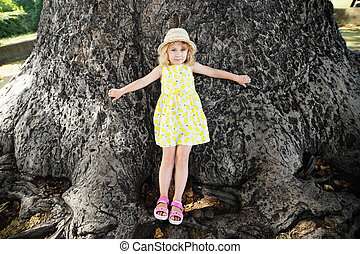 Little girl stands at the base of a very large tulip tree.