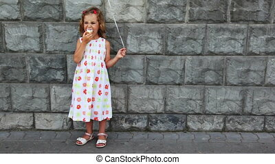 little girl stands, eats ice cream - little girl stands ...