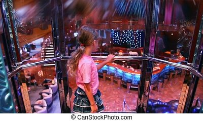 Little girl stands in elevator which lifts from restaurant