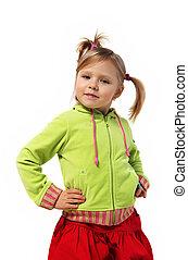 little girl stands near a wall, red skirt, green woman's jacket