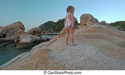Little Girl Stands on Large Bare Rock Top at Sunset on Beach