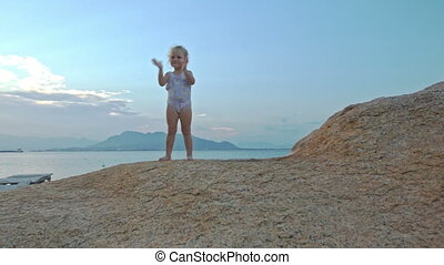 Little Girl Stands on Rock Top Claps Hands at Sunset on Beach