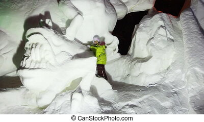girl stands on snow sculptures of animals at artificial...