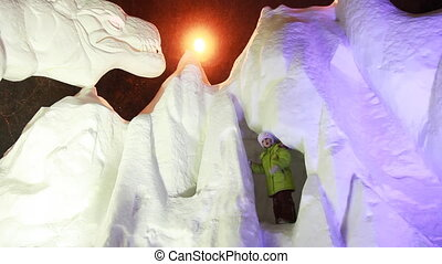 little girl stands on snow sculptures of animals