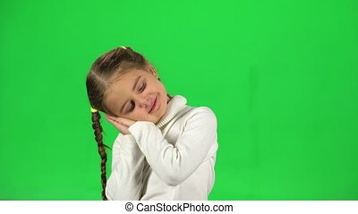 Little girl starts to yawn, she wants to sleep. Green screen. She has two pigtails, dressed in a white sweater