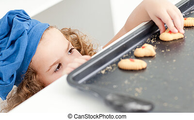Little girl stealing cookies at home