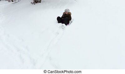 Little girl stepping down the hill and start tobogganing