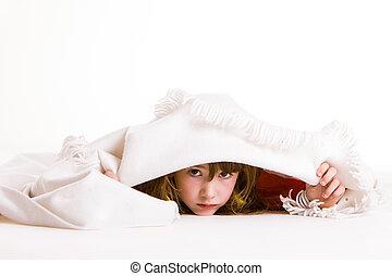 little girl sulking and hiding under a white blanket