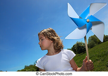 Little girl stood in filed with toy windmill