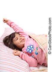 Little girl stretching in bed