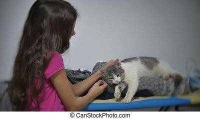 little girl stroking caresses a cat lying on an ironing...