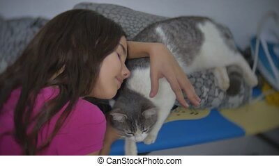 little girl stroking caresses a cat lying on an ironing board. little girl and cat indoors friendship pet slow motion video lifestyle