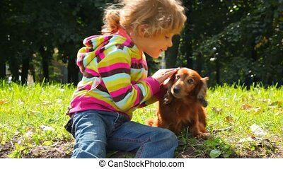 little girl stroking dog in park, looking each other
