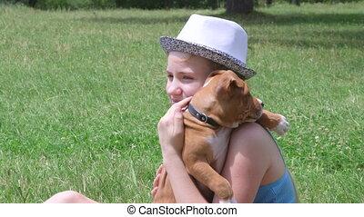 Little girl stroking her puppy dog on grass