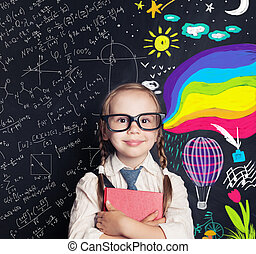Little girl student on blackboard background with chalk math and colorful art pattern. Creativity education, arts and science, right and left hemispheres of the brain concept