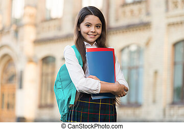 Little girl student school uniform and backpack hold books, formal education concept.