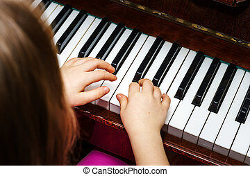 Little girl studing to play the piano