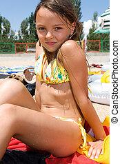 Little girl sunbathing at the beach